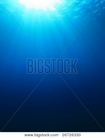 Abstract blue water background of sunbeams in the ocean