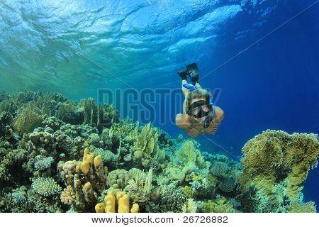 Beautiful Woman snorkeler explores coral reef