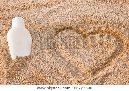 bottle of sun lotion lies in the sand beside a hart