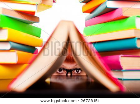 schoolgirl peeking behind books,  funny concept, isolated on white