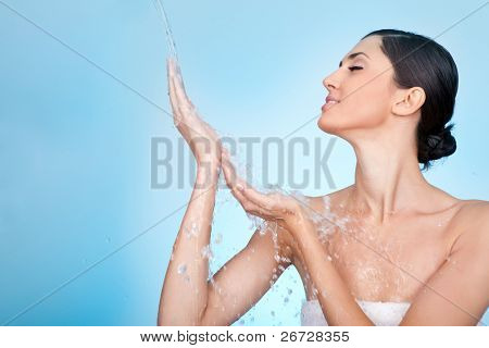 young woman enjoying in water splash on her hands