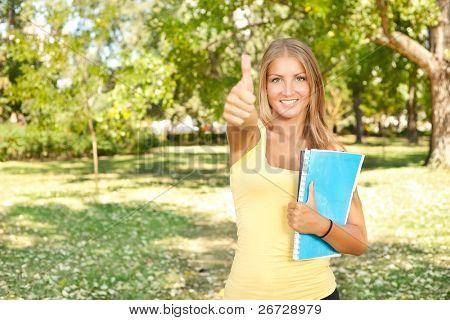 student girl shoving sign ok in park