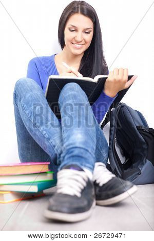 cheerful student girl doing homework, sitting on floor