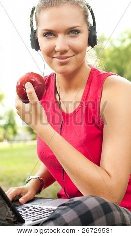 young woman with laptop and headset in park