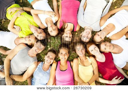 friends happy group in circle heads together on green grass,  outdoor