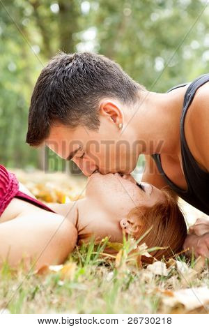 young man kissing his girlfriend in park