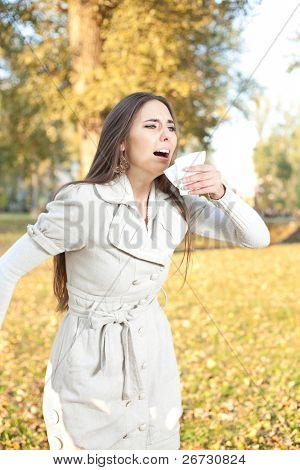 woman with tissue sneezes, outdoor