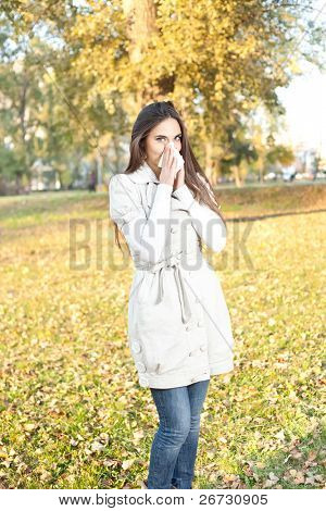 young woman with allergy or cold blowing her nose, outdoor