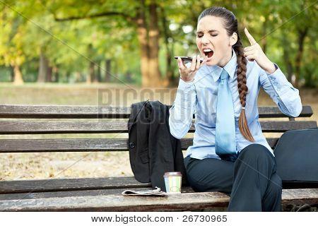 upset businesswoman yelling on mobile phone, outdoor