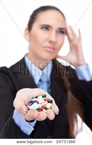 Portrait of a young businesswoman having a migraine and holding handful of pills, isolated on white background