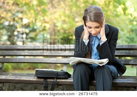 worry businesswoman reading newspaper and holding her head, outdoor