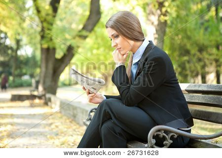 young thinking businesswoman reading newspaper , sitting on bench in park