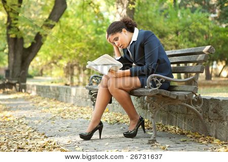young worry businesswoman reading newspaper in park