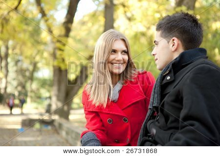 smiling young couple talking in park, girlfriend looking in boy