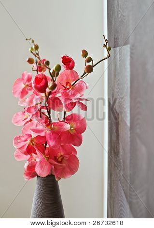 Pink orchid flowers in wicker withe vase
