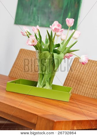 Bouquet of pink tulips flowers in glass vase on wooden table