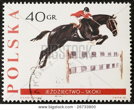 POLAND - CIRCA 1967: a stamp printed in Poland shows image of horse and horseman jumping an obstacle. Poland, circa 1967