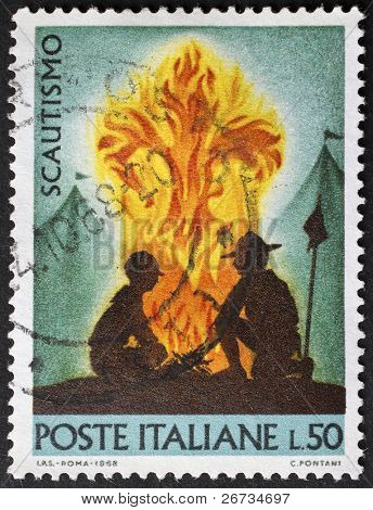 ITALY - CIRCA 1968: a stamp printed in Italy shows image of two scouts crouching near a bonfire, each other in front, as symbol of scout movement. Italy, circa 1968