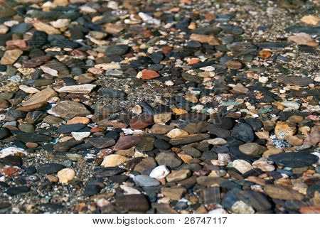 Pebbles under water background. Shallow depth of field. Focus on the center.