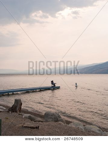 A man relax sitting on pier.