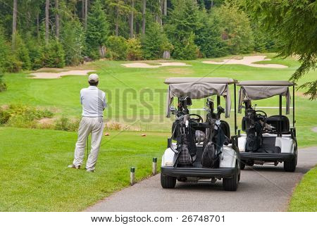 Golfer at teeing area and two carts.