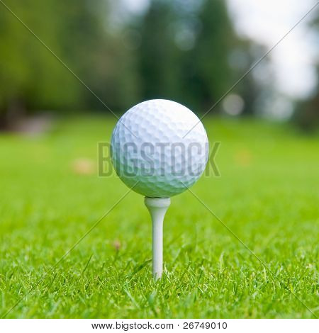 Golf ball on tee over a blurred green. Shallow depth of field. Focus on the ball.