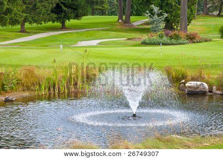 Golf lindo lugar lindo verde, lagoa e fonte.