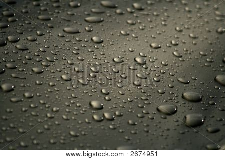 Resting Rain Droplets On Heavily Waxed Car