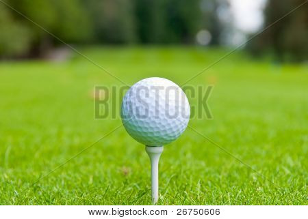 Golfball on Tee über ein unscharfes grün. geringe Schärfentiefe. Fokus auf den ball.