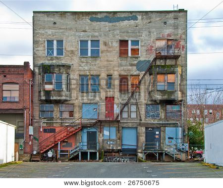 Dilapidated grey old building with stairs in front of it, and blue skies and white clouds above