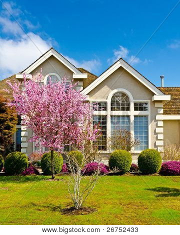 Fragment of a nice house with blossom cherry tree in front in Vancouver, Canada.
