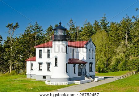A white and red lighthouse over west coast rain forest at sunny day.
