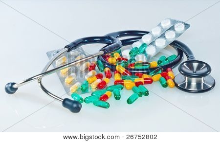 medical concept with colorful pills and stethoscope on white
