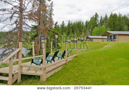 Cabins and picnic chairs with birdhouses on the edge of a lake