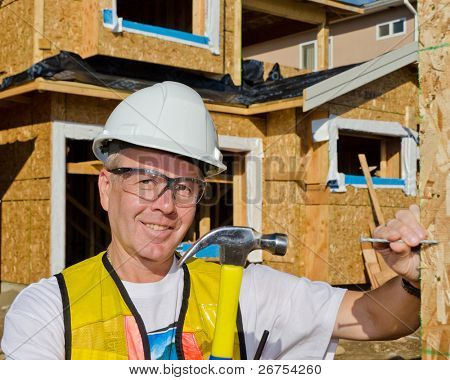 A man in a hard hat standing in front of an house holding a hammer and nail.