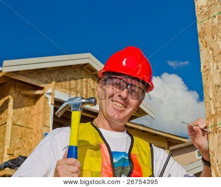 A man in a hard hat standing in front of an house over a blue sky with white clouds at sunny day holding a hammer and nail.