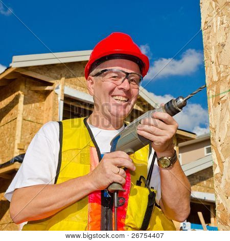 A man in a hard hat standing in front of an house holding a drill in his hand.
