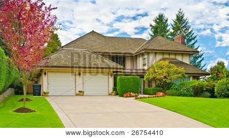 house with double-garage door and outstanding outdoor landscape at sunny day in Vancouver, Canada.