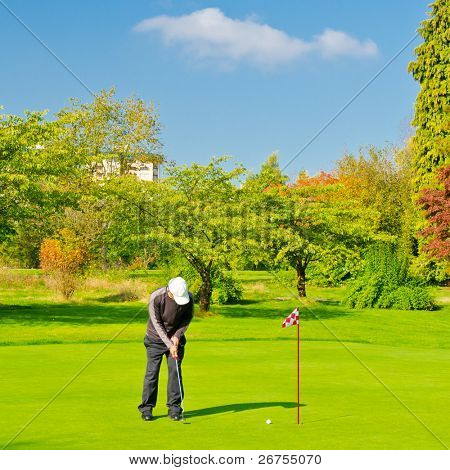 Male golf player pitching off golf ball to the hole, wonderful sky and cloud formation in background.