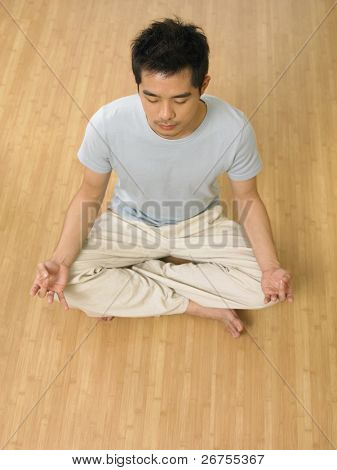 high angle shot of man practicing yoga at home
