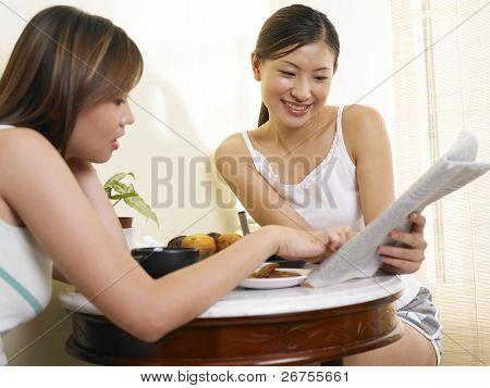 Twoladies reading the newspaper while having a drink