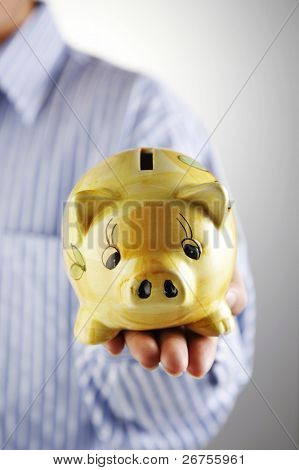 man showing a piggy bank on thew plain  background