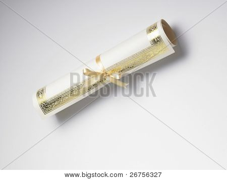 rolled certificate with yellow ribbon on the plain background