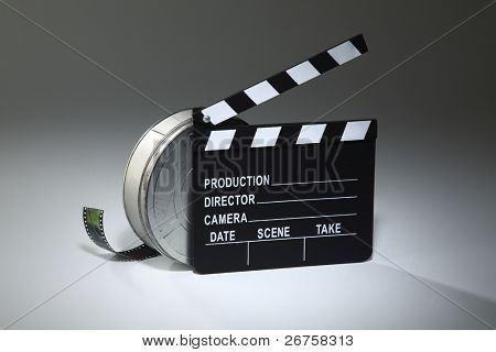 clapperboard and the film reel on the plain background