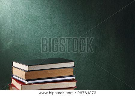 Stapel der Bücher vor dem schwarzen Brett