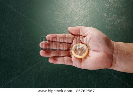 man hand holding a condom