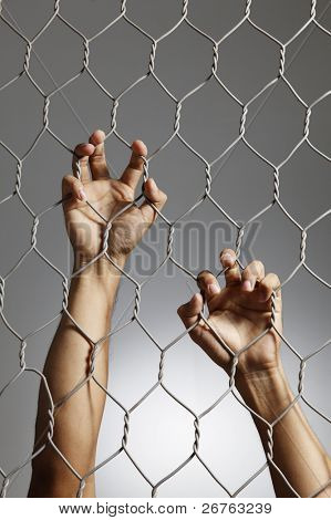 depression - close up of hand on chain-link fence.