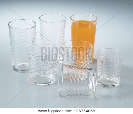 a glass of orange juice and six empty glass on a table top