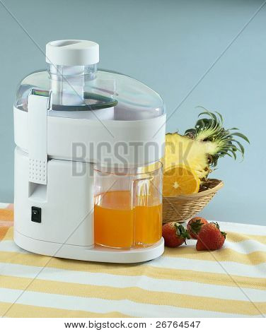 Modern juice extractor with fresh fruits at the side on a white background