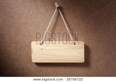 Empty wooden sign hung on background.